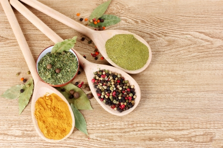 seasonings: spices in the spoons on wooden background