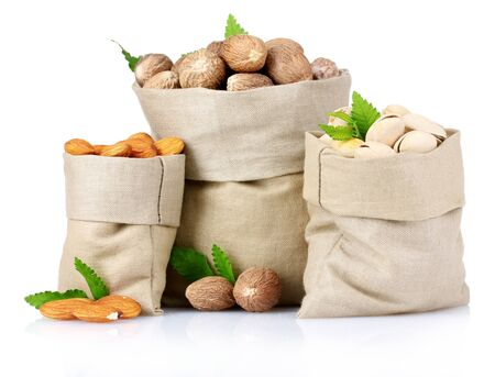 nutmeg, pistachios and almonds in bags on isolated white
