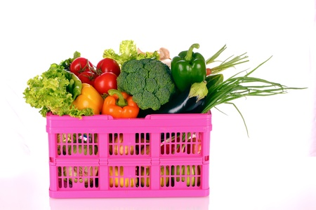 A set of vegetables in plastic basket isolated on white photo