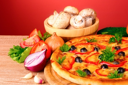 pizza and vegetables on red background photo