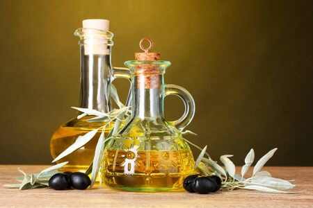 oil and black olives on yellow background