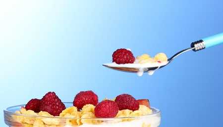 tasty cornflakes, fruit and milk in glass bowl on blue background Stock Photo - 10293437