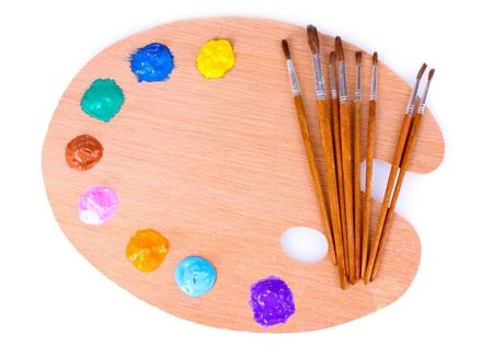 wooden art palette with blobs of paint and a brush on white background Stock Photo - 10293485