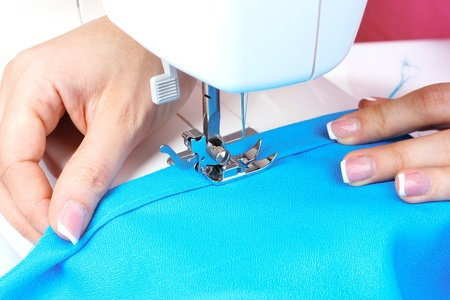 dressmaker: sewing machine, blue fabric and womens hands