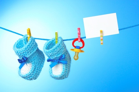 clothes pins: baby booties, nipple and white card on a blue background