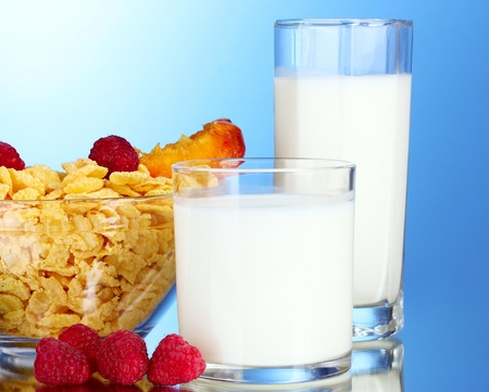 tasty cornflakes, fruit in glass bowl and milk on blue background photo