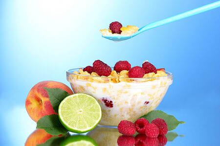tasty cornflakes, fruit and milk in glass bowl on blue background Stock Photo - 10309931