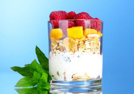 tasty cornflakes, fruit, milk in glass and mint on blue background photo