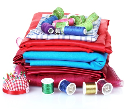 sewing supplies: bright thread, measuring tape and fabric isolated on white
