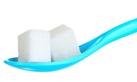 sugar cubes: lump sugar in blue plastic spoon isolated on white