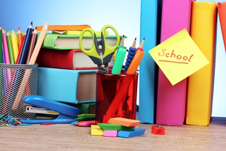 bright stationery and books on blue background photo