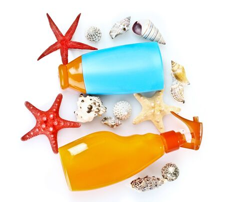 sunblock in bottles and shells isolated on white photo