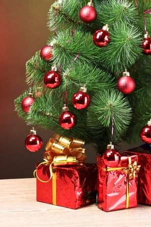 beautiful Christmas tree and gifts on wooden table photo