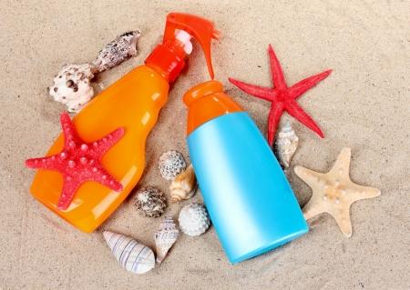 bloqueador solar en las botellas, conchas y estrellas de mar sobre la arena