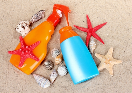sunblock in bottles, shells and starfish on sand photo