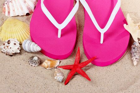 beach shoes, shells and starfish on sand photo