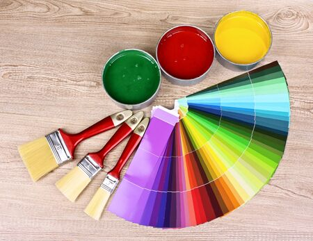 Open cans with bright colors, brushes and palette on wooden background photo