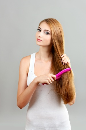 Beautiful young girl with hairbrush on gray background photo