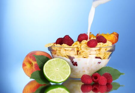 tasty cornflakes, fruit and milk in glass bowl on blue background Stock Photo - 10383531