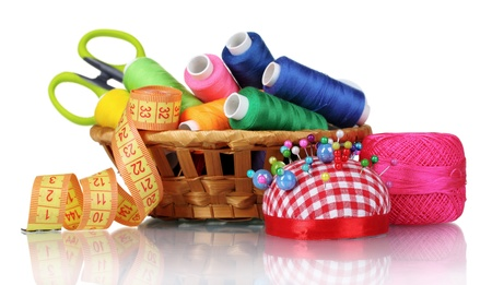 sewing supplies: bright threads in basket, scissors and measuring tape isolated on white Stock Photo