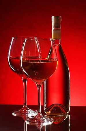 wine bottle and glasses on red background photo