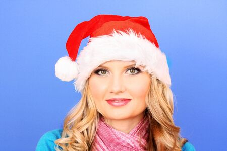 Beautiful girl in  Christmas hat on  blue background photo