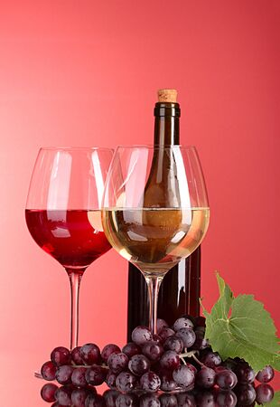 Wine bottle and glass on red background photo