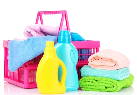 Detergents and towels in basket isolated on white photo
