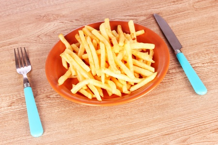 accompaniment: French fries on a plate and cutlery on a wooden background