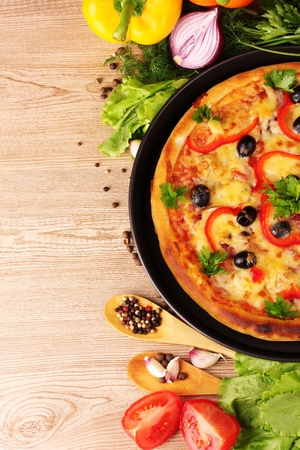 tasty pizza on the plate and vegetables on a wooden background photo