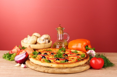 pizza and vegetables on red background Stock Photo - 10383561