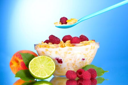 tasty cornflakes, fruit and milk in glass bowl on blue background photo