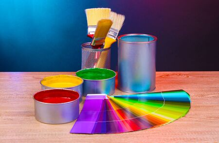 Open cans with bright colors, brushes and palette on wooden table 版權商用圖片