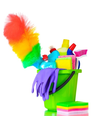 bright housekeeping: detergent bottles, brush, gloves and sponges in bucket isolated on white