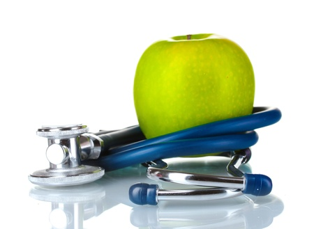 Medical stethoscope and apple isolated on white photo