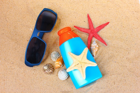 sunblock in bottle, sunglasses, shells and starfish on sand photo