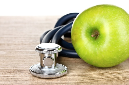 Medical stethoscope and apple on wooden background photo