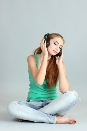 Beautiful young girl with headphones on gray background photo