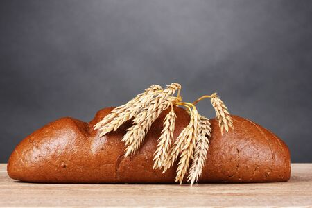 spikelets: rye bread and spikelets on wooden table on gray background