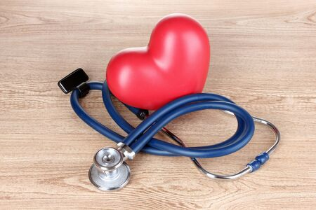 Medical stethoscope and heart on wooden background photo
