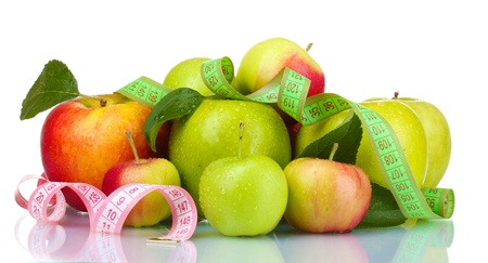 Concept of diet. Many fresh ripe apples with measuring tape isolated on white photo