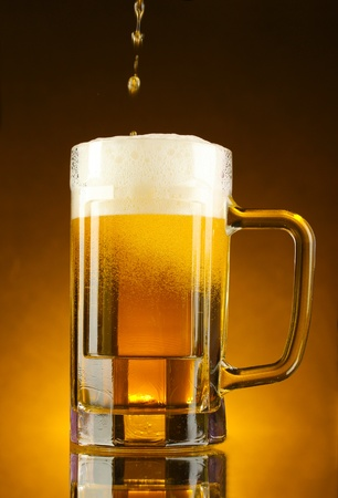 mug of beer on a yellow background photo