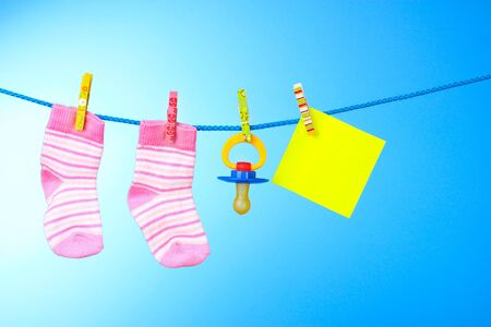 baby booties, nipple and yellow card on a blue background