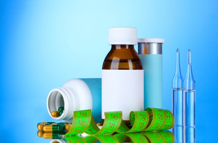 Diet pills and measuring tape on blue background