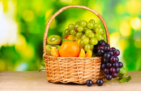 nonfat: Ripe juicy fruits in basket on wooden table on green background