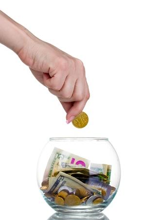 generosidad: Banco de vidrio para consejos con dinero y mano aisladas sobre fondo blanco. Monedas de ucranianas
