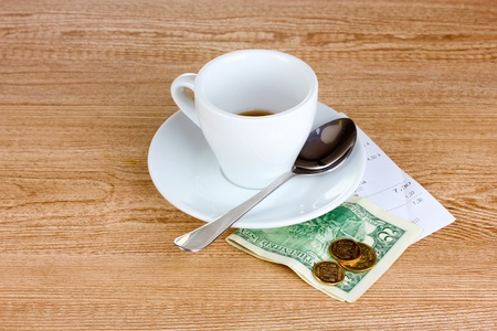 five dollars: Empty cup of coffee with five dollars tip on wooden background. Ukrainian coins