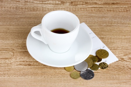 Empty cup of coffee with coins tip on wooden background. Ukrainian coins photo
