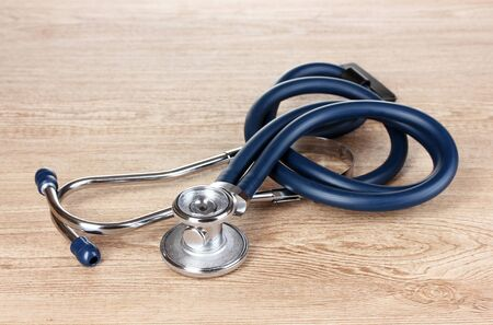 Medical stethoscope on wooden background photo