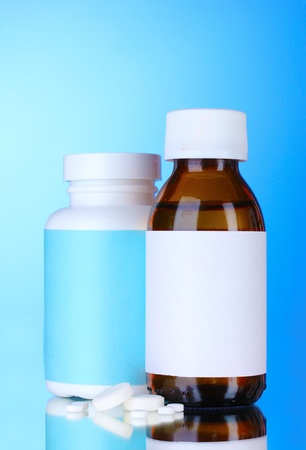 Medical bottles and pills on blue background photo
